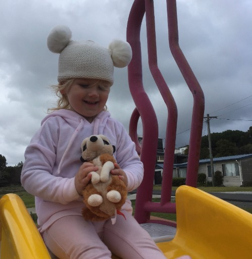 Image description: Child sitting on the top of a slide holding a soft toy