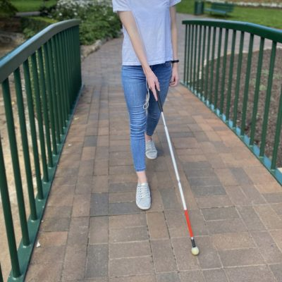 Image description: Client walking across a bridge in a park independently with a white mobility cane