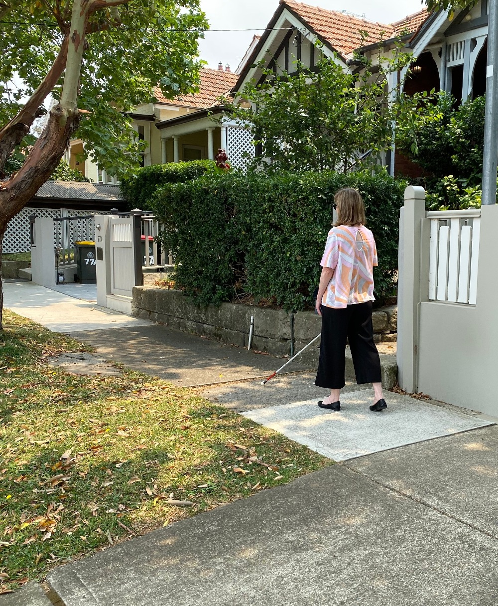 Image description: Woman walking along suburban footpath using a white mobility cane