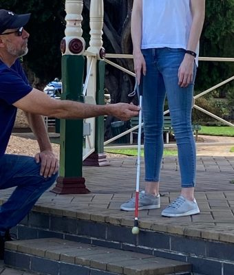 Image Description: Client learning to use white mobility cane to detect stairs going down with O